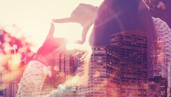 En person skapar en ram med sina fingrar och tittar över en stad