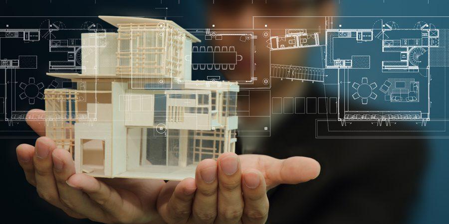 Två händer håller en modell av en byggnad, i bakgrunden syns en planritning