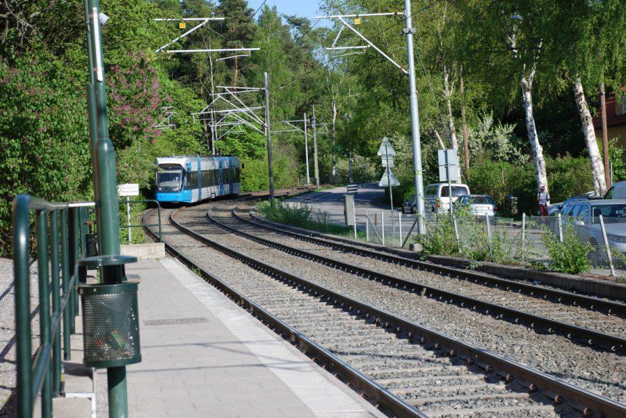 Ett tåg kommer åkande på en räls, bilden är tagen från en perrong