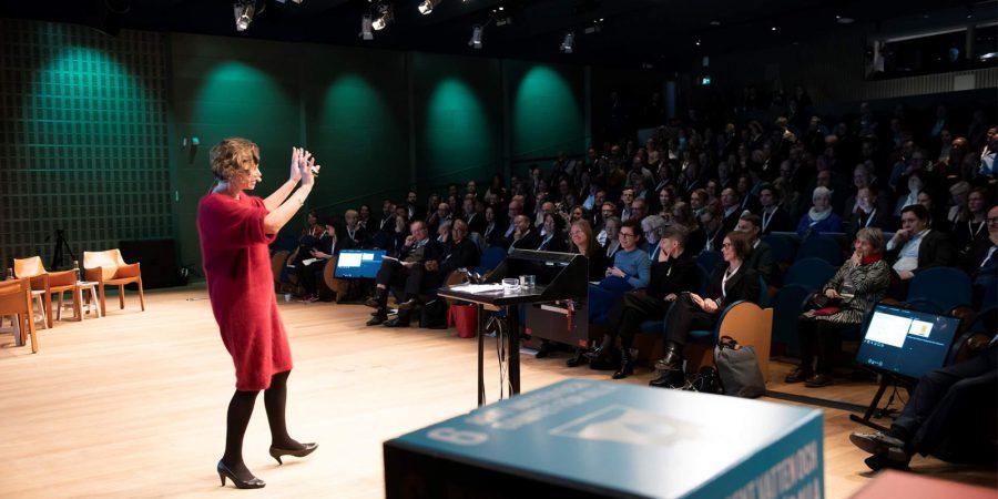 En person med armarna uppsträckta står på en scen framför publik