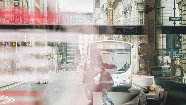 En stadsmiljö, två personer rör sig framför en buss